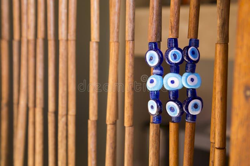 Bunte blaue Amulette auf Türhängendem Bambusdekor stockfotos
