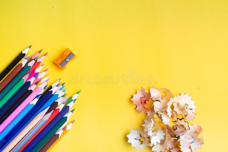 Bunte Bleistifte auf einem gelben Hintergrund Zur?ck zu Schule-Konzept Bleistiftspitzer mit Schnitzeln Copyspace lizenzfreies stockfoto