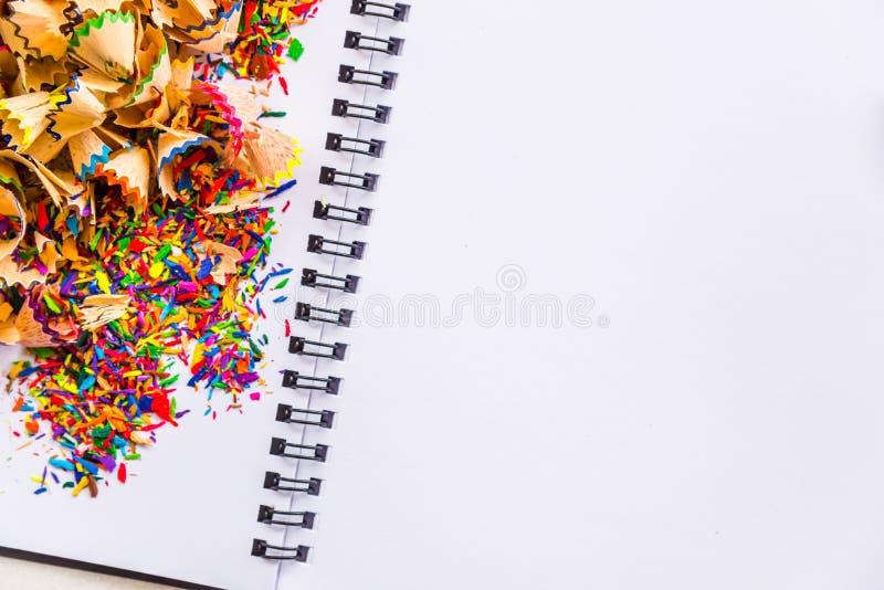 Bunte Bleistifte, die Staub auf Weißbuch rasieren lizenzfreie stockfotos