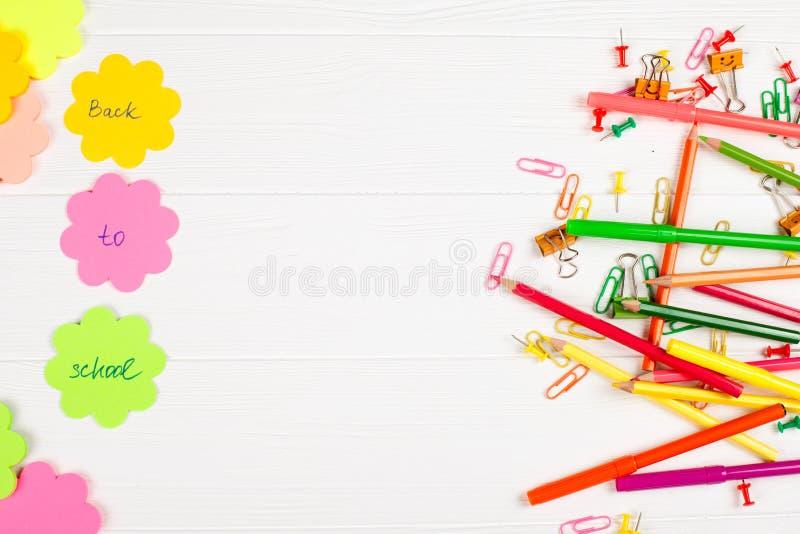 Bunte Bleistifte und Filzstifte, Farbbriefpapier, Büroklammern, Briefpapiernägel auf weißem hölzernem Hintergrund lizenzfreies stockbild