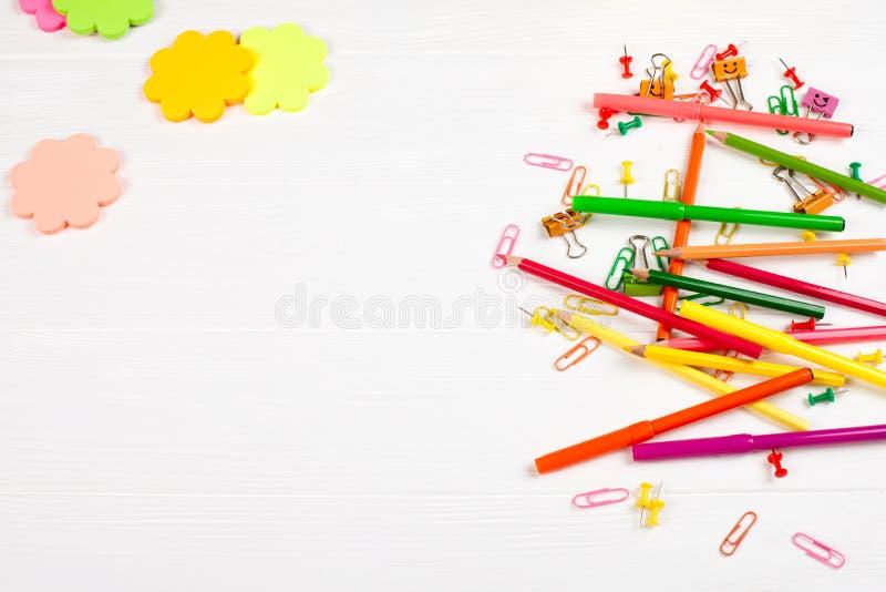 Bunte Bleistifte und Filzstifte, Farbbriefpapier, Büroklammern, Briefpapiernägel auf weißem hölzernem Hintergrund lizenzfreie stockfotos