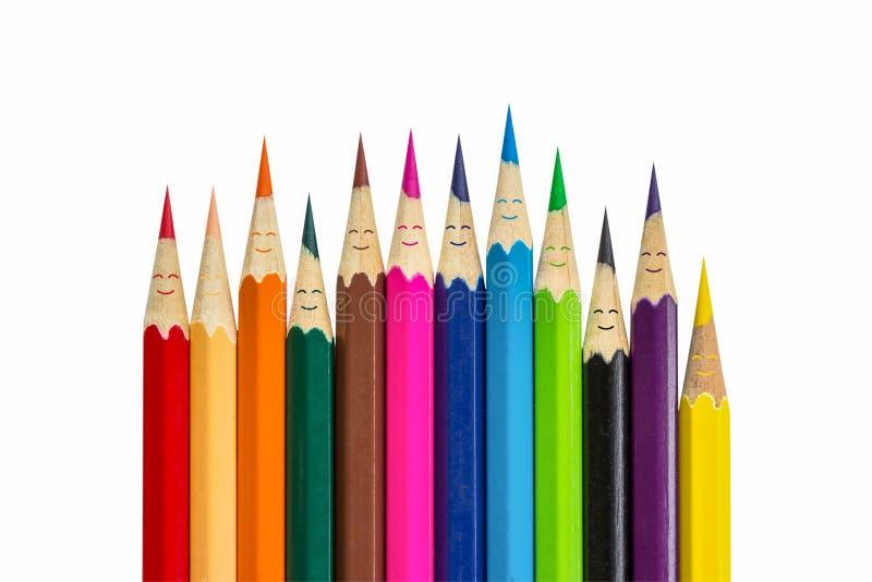 Bunte Bleistifte, wie das Lächeln die lokalisierten Leute gegenüberstellt stockbilder