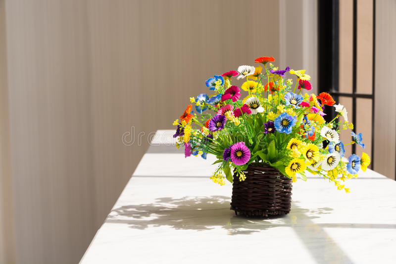 Bunte Blumen in hölzernem Korb Browns neben Glasfenster lizenzfreie stockbilder