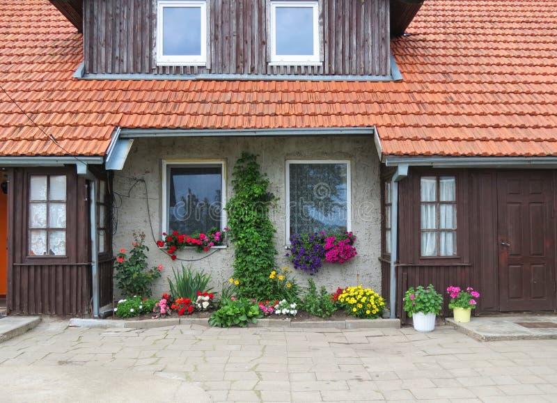 Bunte Blumen nähern sich altem Haus, Litauen lizenzfreies stockfoto