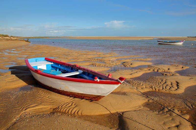 Bunte Boote, die bei Sonnenuntergang auf dem Strand von Cacela Velha, ein kleines Dorf gelegen nahe Tavira, Algarve festmachen lizenzfreie stockbilder