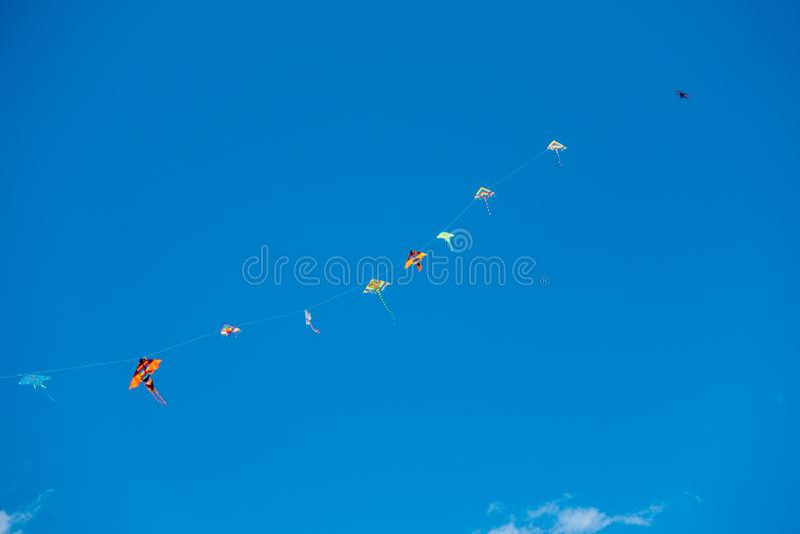 Bunte Bremsungsdrachen, die in den blauen Himmel fliegen stockbild