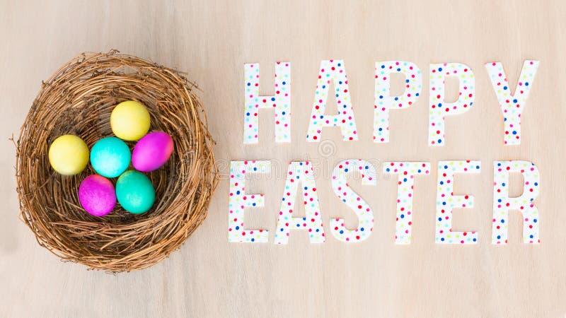 Bunte Eier im Nest, hölzerner Hintergrund Flache Lage, Kopienraum, ha stockfotografie