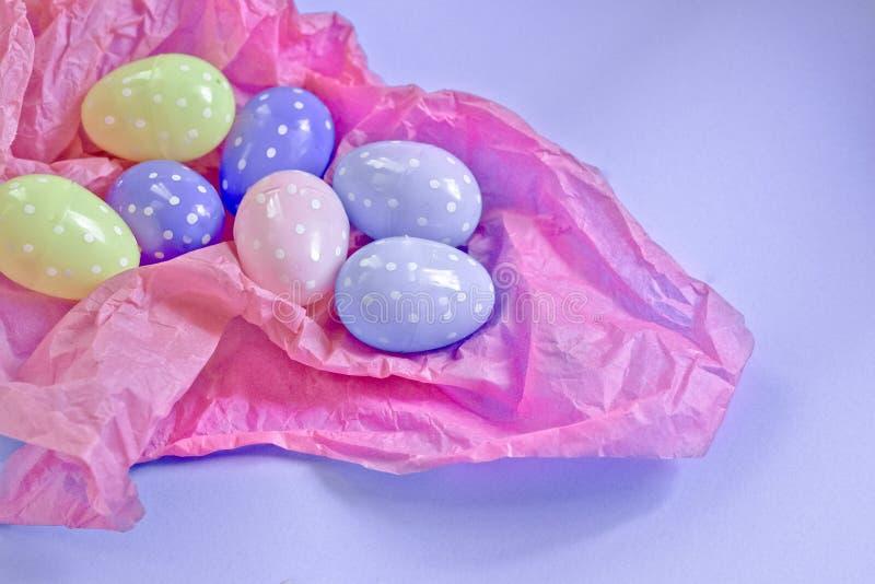 Bunte Eier mit dem weißen Tupfenmuster, das auf das Papier legt stockfotografie