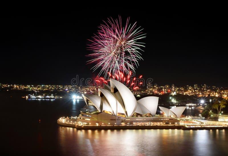 Bunte Explosionen von Feuerwerken füllen den nächtlichen Himmel bei Sydney Opera House stockfotografie