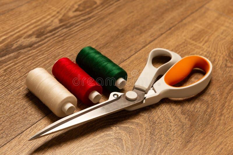 Bunte Fadenspulen und -scheren auf Werkbank stockfotografie