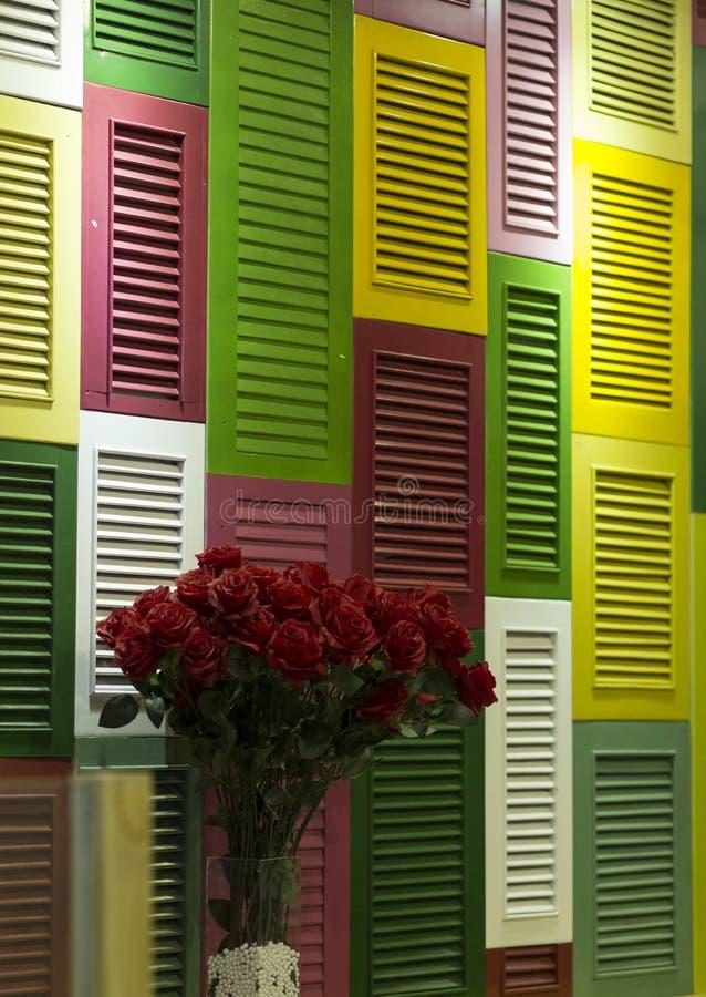 Bunte Fensterläden und Blumenstrauß von roten Rosen lizenzfreies stockfoto