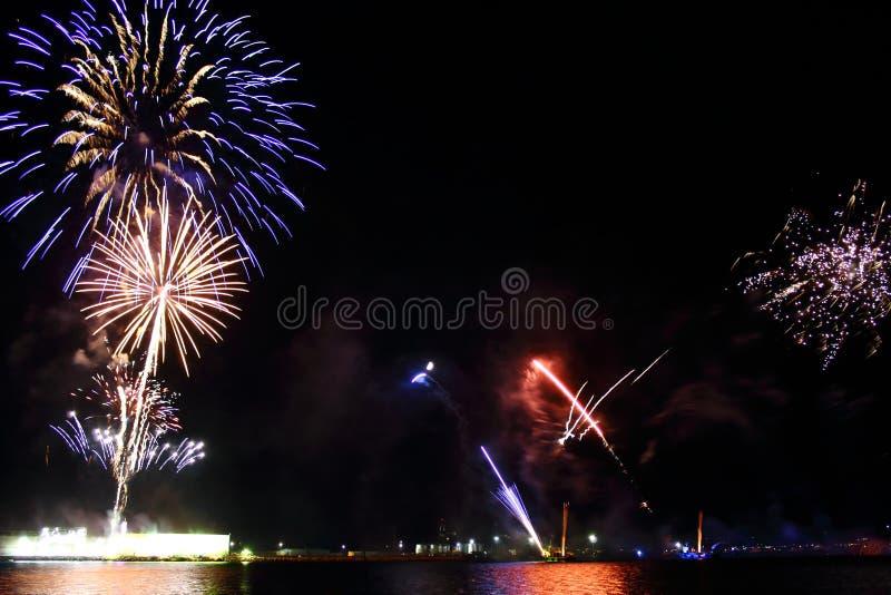 Bunte Feuerwerke auf dem schwarzen Himmelhintergrundüberwasser lizenzfreies stockfoto