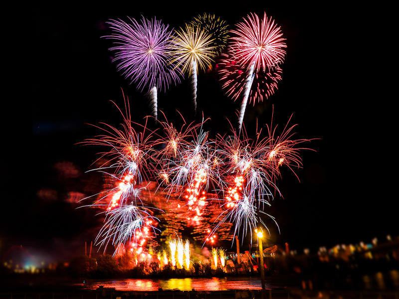 Bunte Feuerwerke mit mehrfachen Explosionen gegen bewölkten Himmel lizenzfreie stockbilder