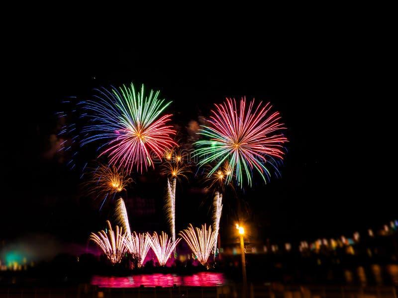Bunte Feuerwerke mit mehrfachen Explosionen gegen bewölkten Himmel stockbild