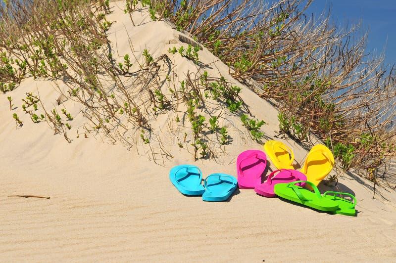 Bunte Flip Flop-Sandalen auf einem Strand stockfoto