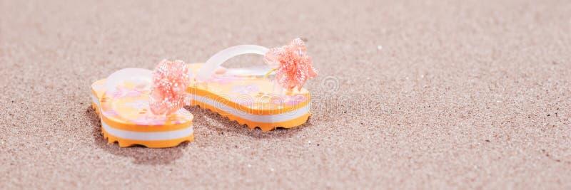 Bunte Flipflops auf dem sandigen Strand stockfotografie