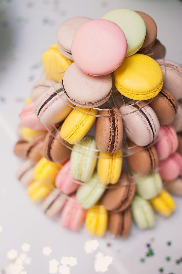 Bunte französische macarons mehrstufige Kuchenpyramide auf Plastiknachtischstand stockfoto