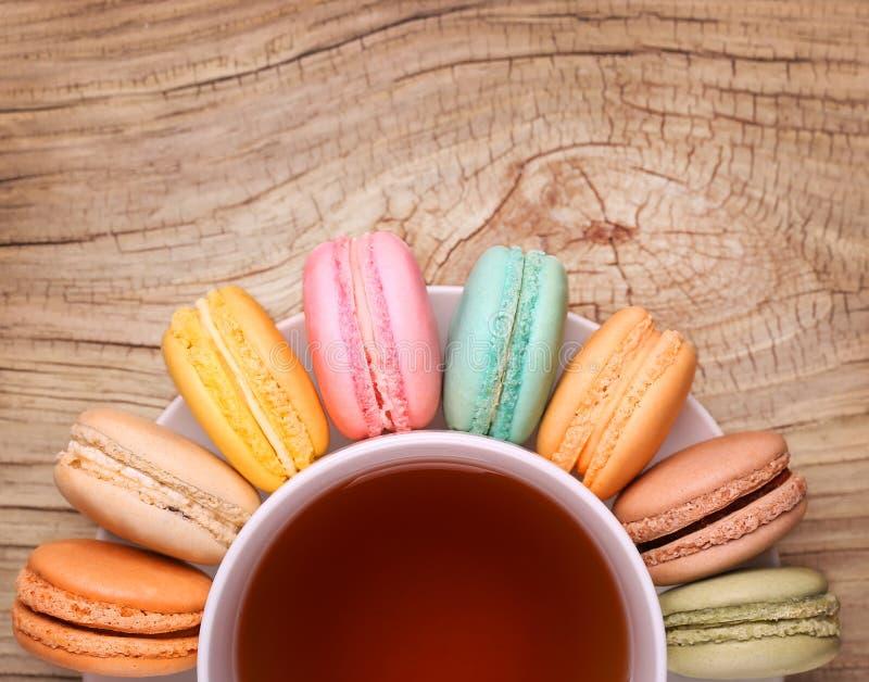 Bunte Franzosen Macarons mit Tasse Tee lizenzfreie stockfotografie