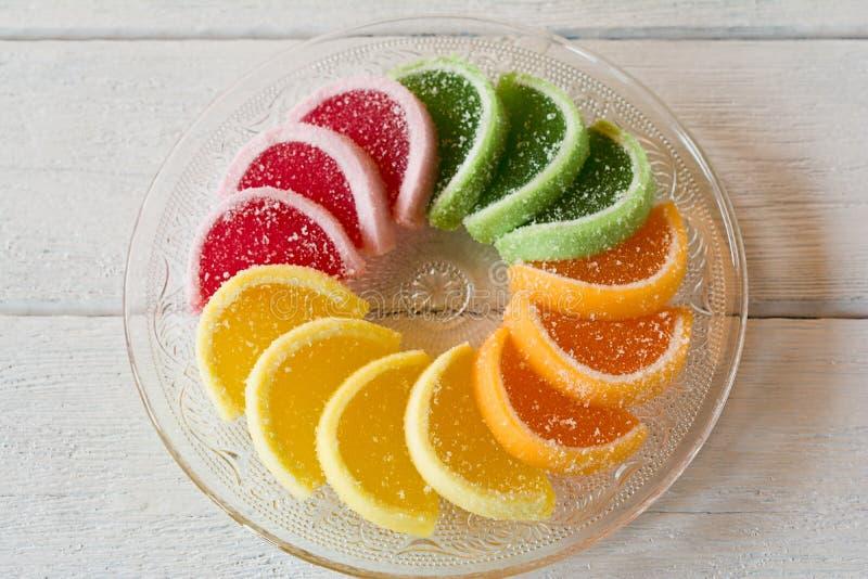 Bunte Fruchtgeleesüßigkeiten vereinbarten im Kreis auf Holztisch stockfotos