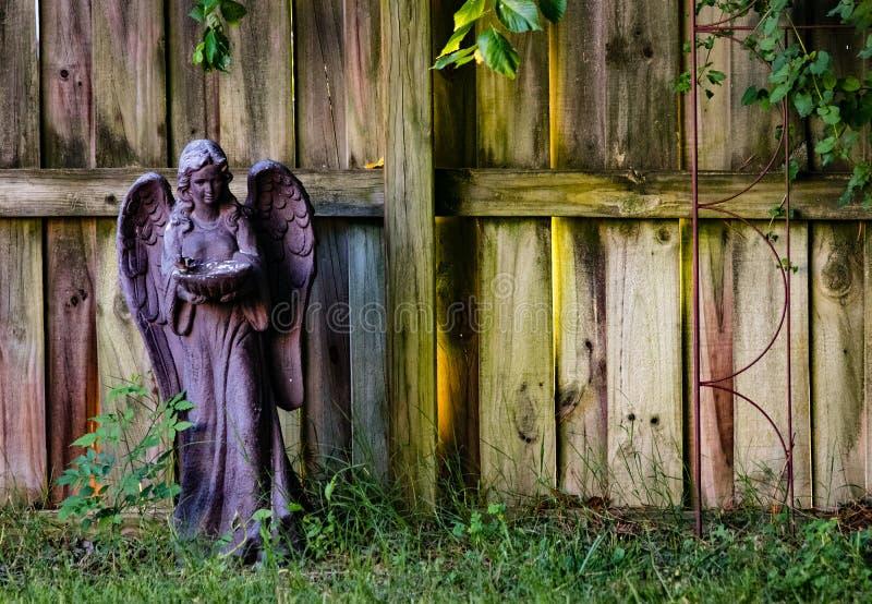 Bunte Gartenstatuette gegen verwitterten Zaun stockfotografie