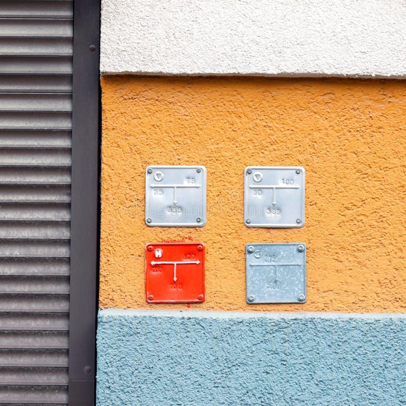 Bunte Gebäudewand mit Zeichenplatten für Erdgas leitet lizenzfreie stockfotos