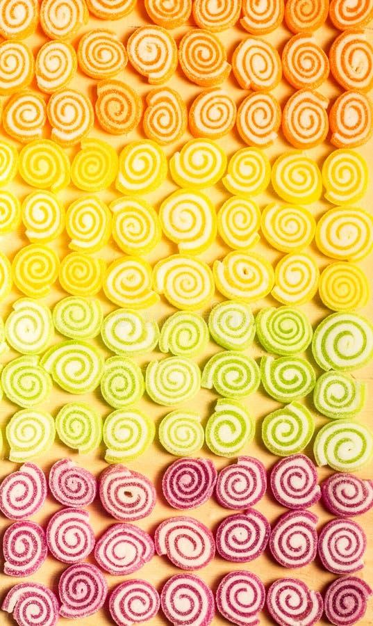 Bunte Gelees und Süßigkeitsbonbons auf hölzernem Hintergrund stockbilder