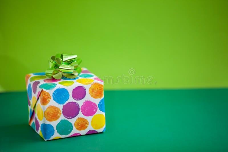 Bunte Geschenkbox auf Kalkfarbhintergrund Explosion von Farben und von Formen stockfoto