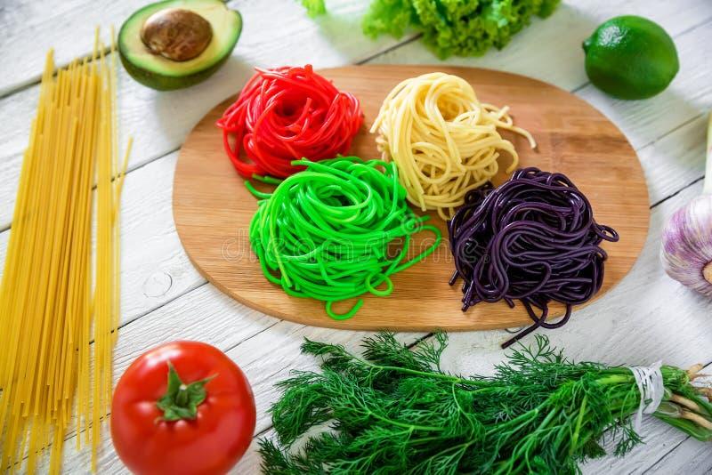 Bunte geschmackvolle Teigwaren an Bord und rohes Gemüse auf rustikaler Tabelle Flache Lage Beschneidungspfad eingeschlossen stockfoto