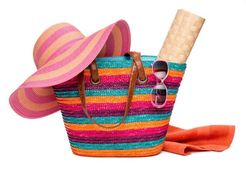 Bunte gestreifte Strandtasche mit einem Hutsonnenmatte Tuch und sunglass stockbilder
