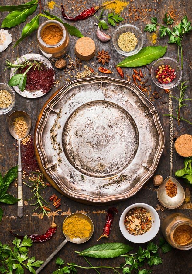 Bunte Gewürze und Kräuter mit Löffel um leere Weinlesemetallplatte auf rustikalem hölzernem Hintergrund lizenzfreie stockfotos