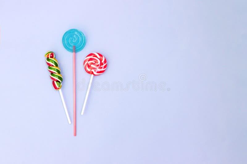 Bunte gewundene Lutschersüßigkeiten auf blauem Hintergrund Minimales Konzept mit Kopienraum Flache Lage lizenzfreie stockfotografie