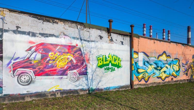 Bunte Graffiti mit rosa Packwagen und chaotischen Textelementen stockbild