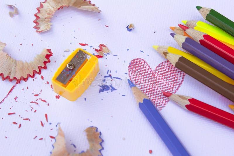 Bunte Gruppe Bleistiftzeichenstifte, -bleistiftspitzer und -schnitzel vom Schärfen auf einem Weißbuchhintergrund Bildungsrahmenko lizenzfreie stockbilder