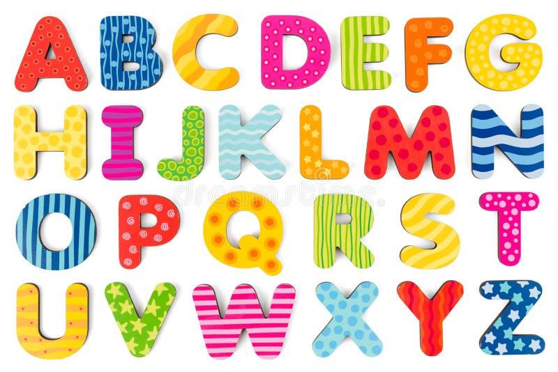 Bunte hölzerne Alphabetbuchstaben auf einem weißen Hintergrund stockbilder