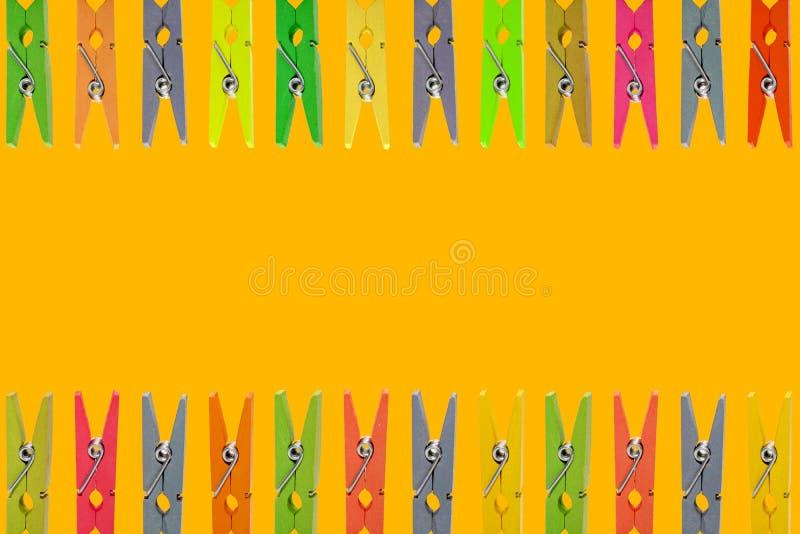 Bunte hölzerne Wäscheklammern auf gelbem Hintergrund lizenzfreie stockfotos