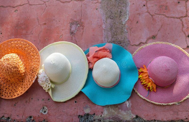 Bunte Hüte, die an einer rosa Wand hängen lizenzfreie stockbilder