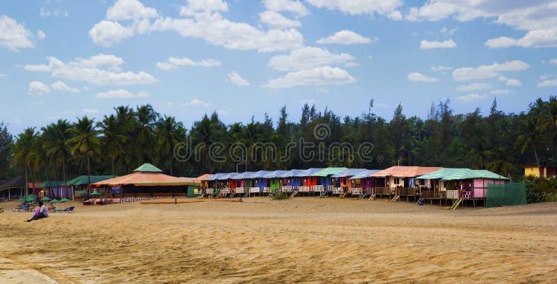 Bunte Hütten in Agonda setzen mit Palmehintergrund in Goa, Indien auf den Strand lizenzfreies stockbild