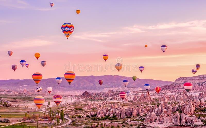 Bunte Heißluft steigt das Fliegen über Felsenlandschaft bei Cappadoc im Ballon auf stockbilder