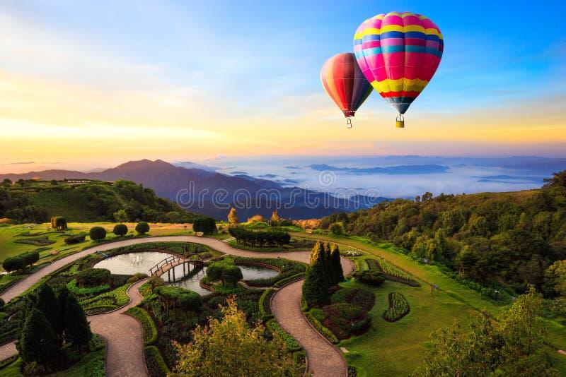Bunte Heißluftballone, die über den Berg fliegen stockbilder