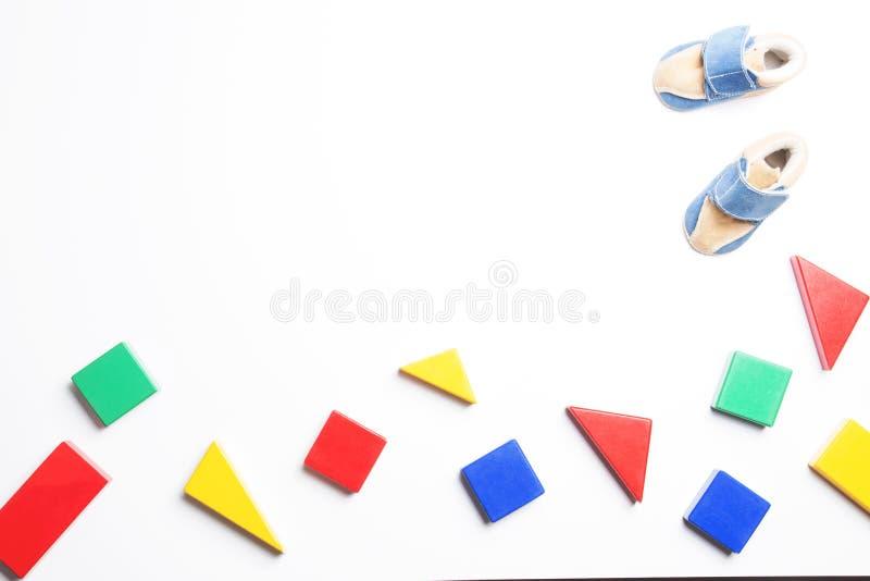 Bunte Holzklötze und Babyschuhe auf weißem Hintergrund stockbilder