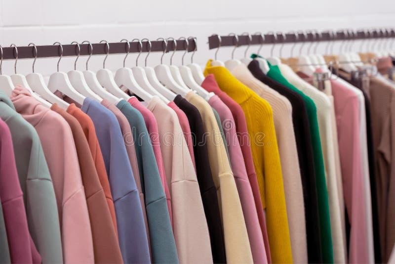 Bunte Jugendkaschmirstrickjacken und Kapuzenpullis, Sweatshirts und auf einem Kleiderständer im Speicher stockfotografie