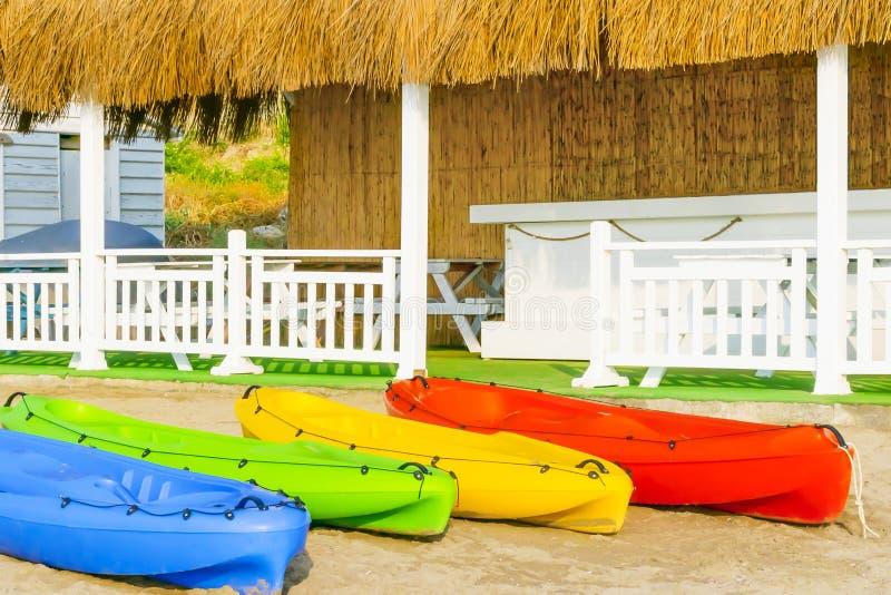Bunte Kajaks auf weißem Sand auf dem Strand von Zypern gegen Sommerhaus mit weißem Bretterzaun und Reeddach stockbild