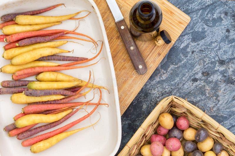 Bunte Karotten und Kartoffeln mit Schneidebrett stockbilder