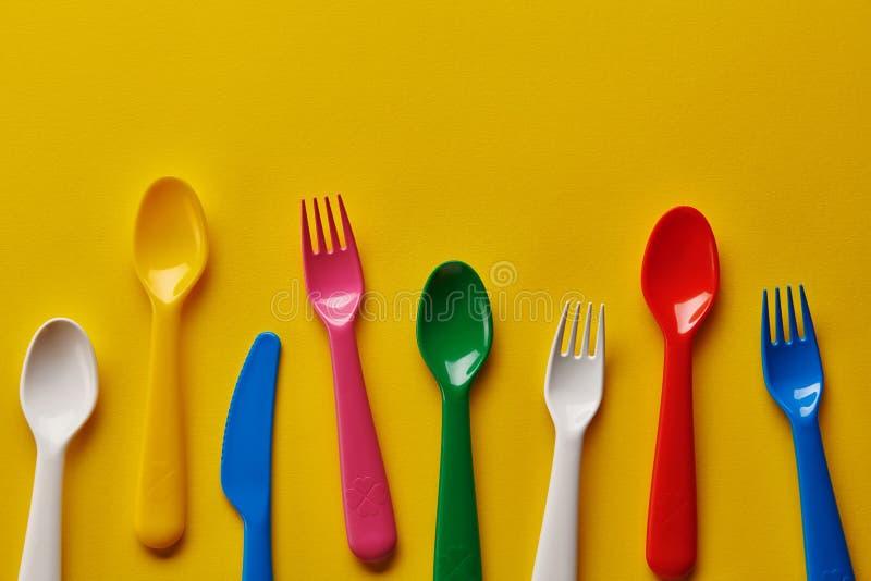 Bunte Kinderplastiklöffel auf gelbem Hintergrund Viele, Geräte lizenzfreies stockfoto