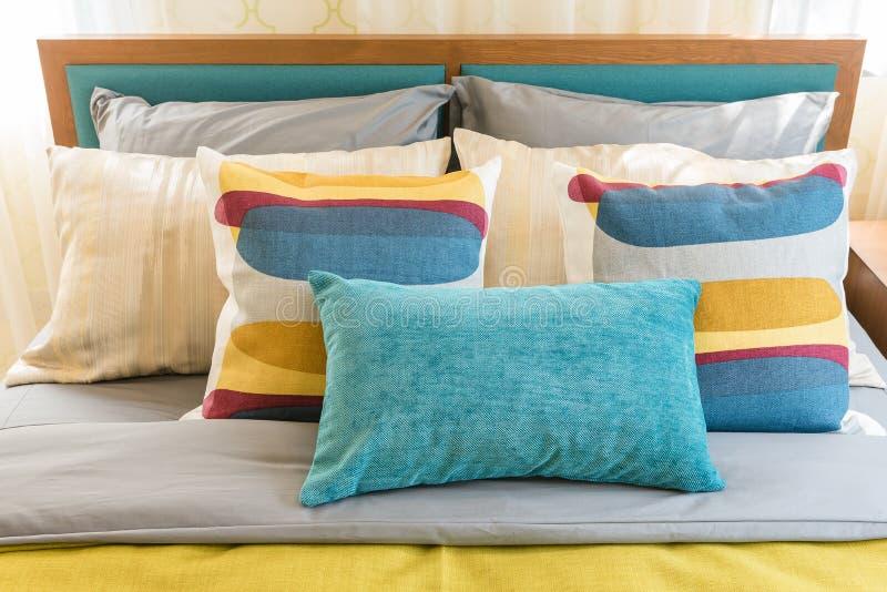 Bunte Kissen auf hölzernem Bett im modernen Schlafzimmer stockbild