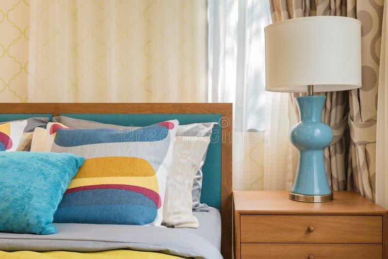 Bunte Kissen auf hölzernem Bett im modernen Schlafzimmer lizenzfreies stockfoto