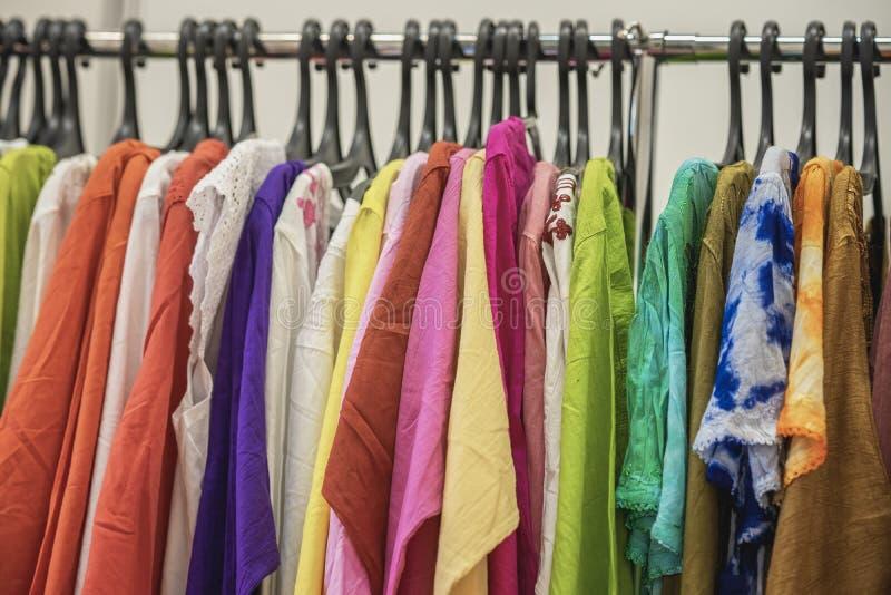 Bunte Kleidung auf Aufhängern für Verkauf im Geschäft Sommersaison, Zusammenstellung in einem Bekleidungsgeschäft Wahl von Baumwo stockfotografie