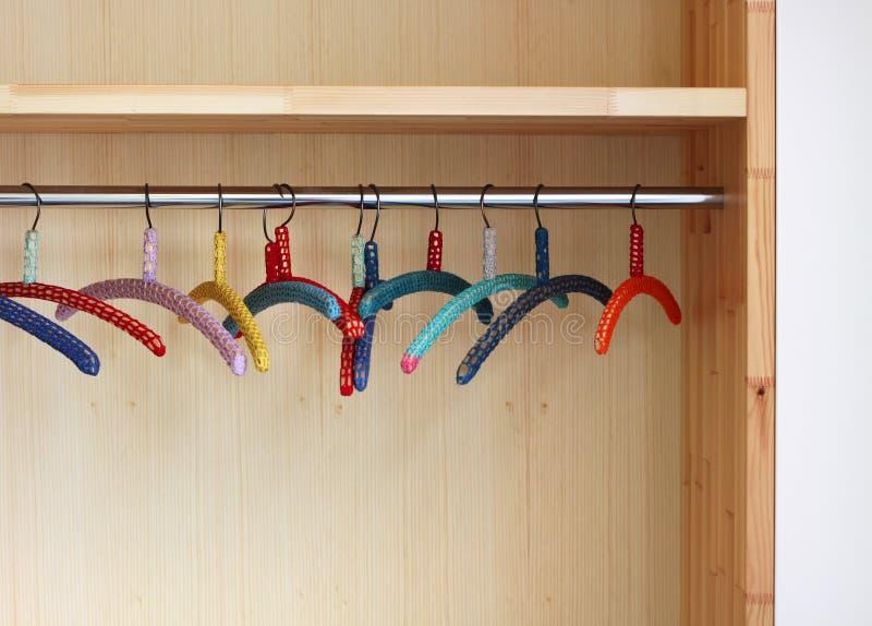 Bunte Kleidungaufhängungen im Wandschrank lizenzfreie stockbilder