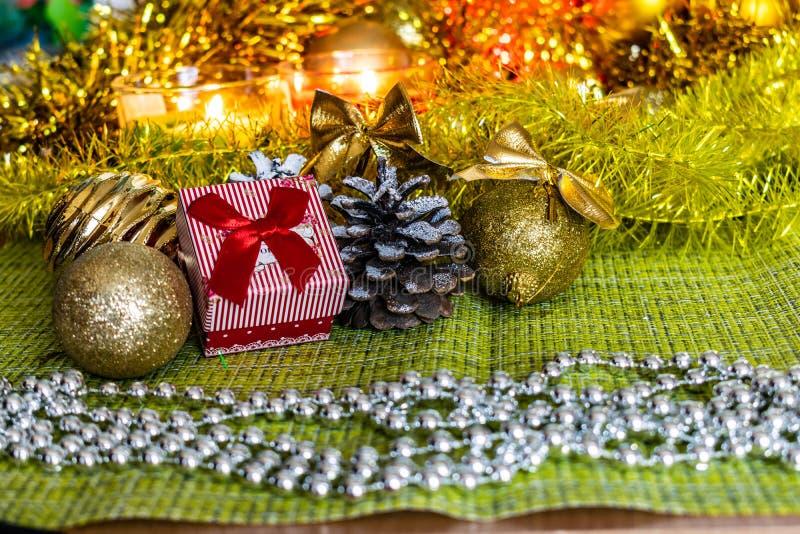 Bunte kleine Geschenkboxen mit Geschenken unter Weihnachtslametta und glänzende Spielwaren und Dekorationen stockfoto