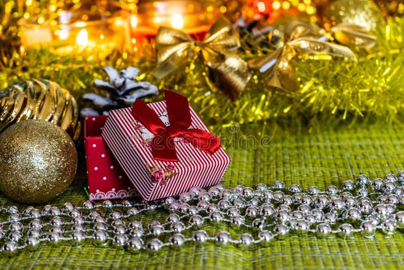 Bunte kleine Geschenkboxen mit Geschenken unter Weihnachtslametta und glänzende Spielwaren und Dekorationen stockbild